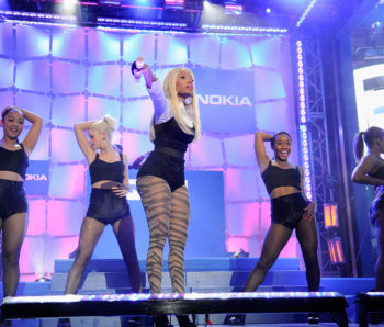 """NEW YORK, NY - APRIL 06:  A general view of the atmosphere as Times Square was brought to a standstill on April 6, 2012 as Nicki Minaj teamed up with Nokia to perform live for the launch of the Windows Phone-based Nokia Lumia 900 in North America, in New York City. Tens of thousands of people watched Nicki perform a medley of her hits before a prominent Times Square building was turned into a living, breathing entity in time to the unique Nokia Lumia 900 remix of her hit single 'Starships'. The building appeared to fill with water before a 60ft waterfall was seen to cascade down the side of the building. The reaction of the crowd was shown on nine massive electronic screens around the famous square making it one of the biggest LED displays ever seen and will be used in the video of Nicki's new Nokia Lumia 900 remix of 'Starships'. The singer said: """"When Nokia came to me with the idea to make a building come alive and to perform in Times Square in front of my fans to celebrate the launch of the Nokia Lumia 900 there was only ever one answer. To see the idea on paper was amazing but to see it for real blew me away. It brought Times Square to a standstill. The absolute bonus for me is that my fans, who have been so loyal to me, are now part of the video for the Starships Nokia remix. Performing in my home town of NYC the same week as the release of my new album, Pink Friday: Roman Reloaded is amazing and it really is a dream come true.""""  The Nokia Lumia 900 will be available in unique and eye-catching cyan blue and a matte black with a new high-gloss white version on sale later this month. To watch more of the amazing event go to www.facebook.com/nokiaus  (Photo by Kevin Mazur/Getty Images for Nokia) *** Local Caption *** Nicki Minaj"""